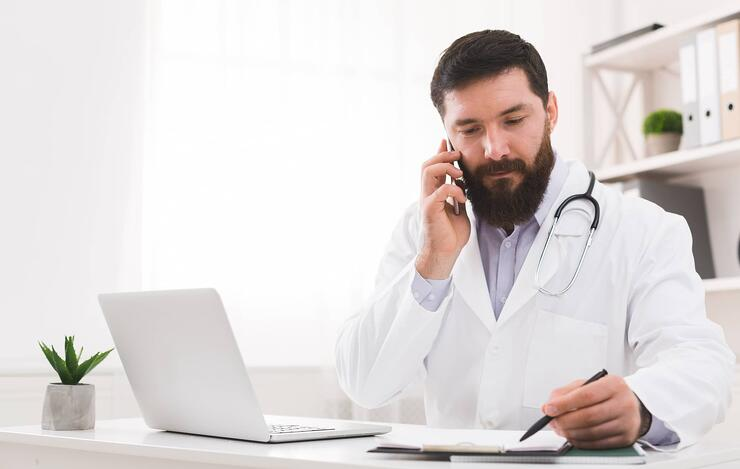 Doctor-talking-with-his-patient-and-writing-down-diagnosis-1084535418_2179x1381